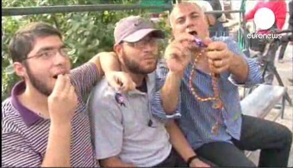 Men in Gaza celebrate with sweetcakes upon hearing news of bus bombing in Tel Aviv