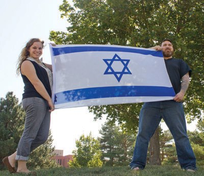 Rachel and Tim hoisting an Israeli flag | Courtesy Andy Engelmann