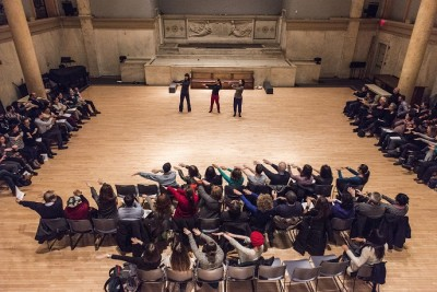 """Schiff teaches the audience how to spell """"DRY"""" with their bodies before the show. Photo credit: Jun Chang."""