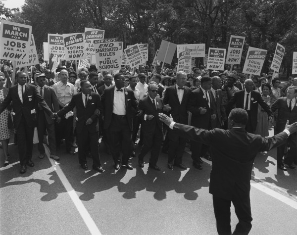 Jewish civil rights activist Joseph L. Rauh, Jr. marches with Martin Luther King in the 1963 March on Washington. | By United States Information Agency, Licensed under Public Domain via Commons.
